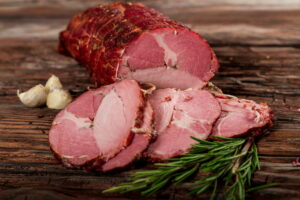 Gypsy Ham sliced with garlic and rosemary displayed on aged wood - made from selected pork cuts – the neck filet and tenderloin – seasoned baked and smoked with beech wood