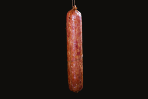 Homemade Salami hanging by a string on black background - made from selected pork ham and pork meat - cured by boiling and slow smoking with beech wood – seasoned with garlic black pepper allspice coriander and paprika