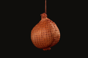 Rooster Ham hanging by a string on black background – made from top quality rooster breast meat – cured by brining with garlic paprika and white pepper - boiling and slow smoking with various hardwood essences