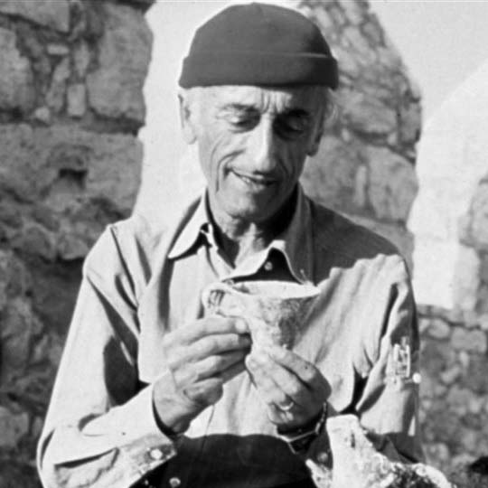 black and white photo of Captain Jacques-Yves Cousteau checking an ancient cup