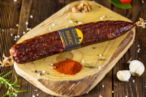 Babic Salami with garlic rosemary and red paprika displayed on aged wood - made with a mixture of pork and beef – air dried – smoked - seasoned with salt sweet and hot paprika then stuffed into thin beef casings and hand pressed