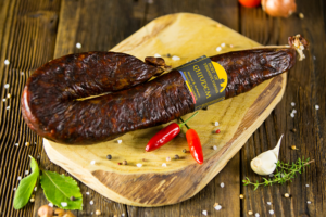 Ghiudem Salami with garlic and red paprika displayed on aged wood - made with a mixture of sheep and beef – air dried – smoked - seasoned with SALT PAPRIKA GARLIC and PEPPER
