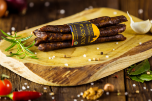 Plescoi Sausage with garlic and rosemary displayed on aged wood - made from the right balance of beef and sheep – air dried – smoked - seasoned with SUMMER SAVORY SALT PAPRIKA GARLIC and PEPPER