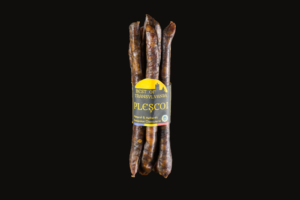 Plescoi Sausage hanging by a string on black background – made from the right balance of beef and sheep – air dried – smoked - seasoned with SUMMER SAVORY SALT PAPRIKA GARLIC and PEPPER