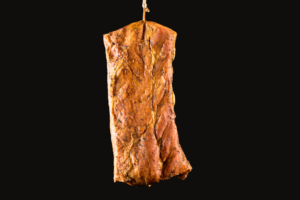 Rustic Tenderloin hanging by a string on black background – made from specially selected pork belly – cured by boil with spices - double smoked with oak wood